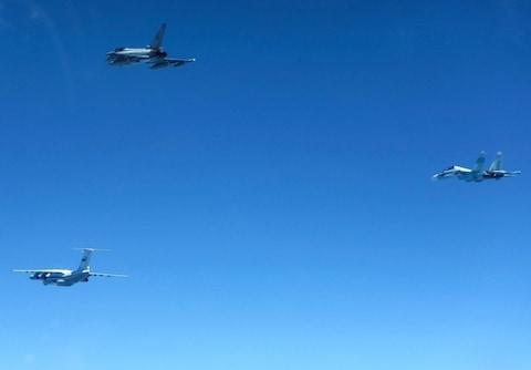 A Russian IL-76 Candid transport plane (L) and an SU-30 Flanker fighter (R) shepherded by an RAF Typhoon fighter (C). June 15, 2019. - Credit: RAF/REX