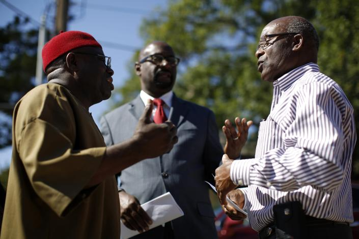 Steve Oriabure (R), Vice board Chairman of the Organization of Nigerian Nationals, speaks to Richard Nwachukwu (L), member of the Organization of Nigerian Nationals, and U.S. Congressional candidate Eric Williams after speaking to the media about their concerns on the impact of the Ebola crisis on the African communities in Dallas, Texas, October 4, 2014. REUTERS/Jim Young (UNITED STATES - Tags: HEALTH DISASTER)
