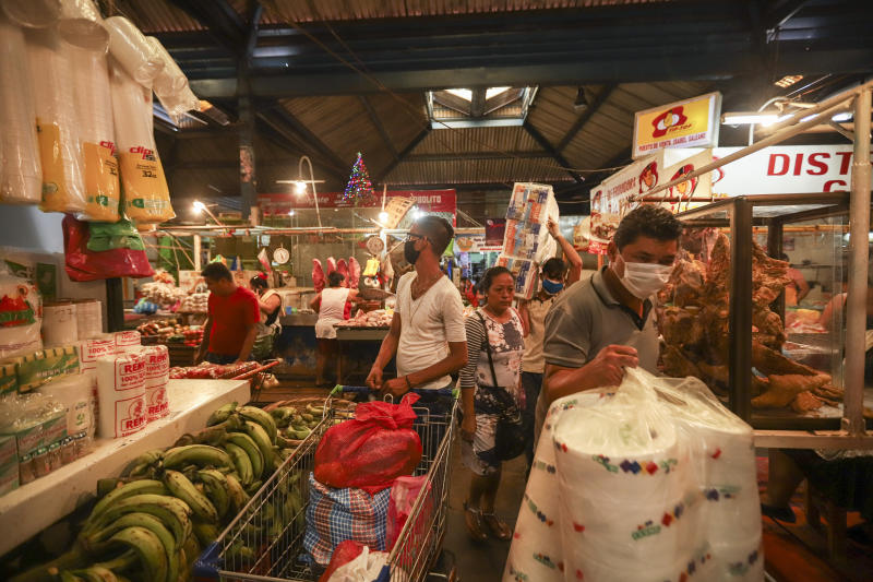 Customers, some wearing protective face masks, shop at a popular market in Managua, Nicaragua, Tuesday, April 7, 2020. Restaurants are empty, there's little traffic in the streets and beach tourists are sparse headed into Holy Week despite the government's encouragement for Nicaraguans to go about their normal lives. (AP Photo/Alfredo Zuniga)