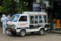 Ambulance and medical staff stand near a a vehicle carrying the body of a person who died of Covid-19 at Siliguri District hospital. The decision to begin the now-suspended IPL in the face of a deepening health crisis has prompted criticism from observers