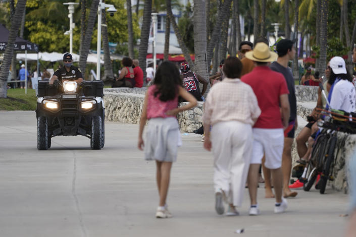 A police officer on an ATV patrols in Miami Beach, Florida's famed South Beach, Monday, March 22, 2021. A party-ending curfew is in effect in Miami Beach, imposed after fights, gunfire, property destruction and dangerous stampedes broke out among huge crowds of people. The curfew could extend through the end of spring break. (AP Photo/Wilfredo Lee)