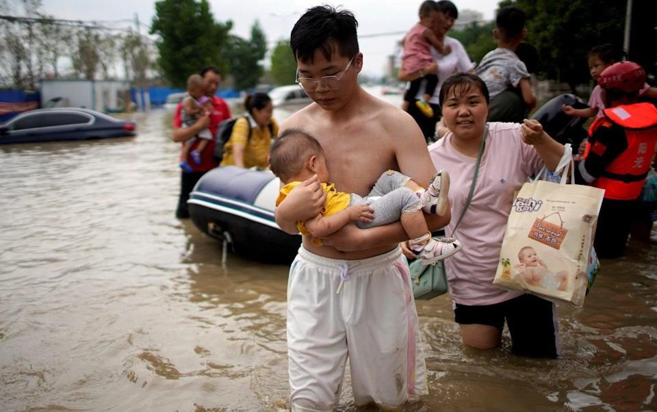 Families were forced to flee after extremely high levels of rain flooded parts of Henan - REUTERS/Aly Song/File Photo