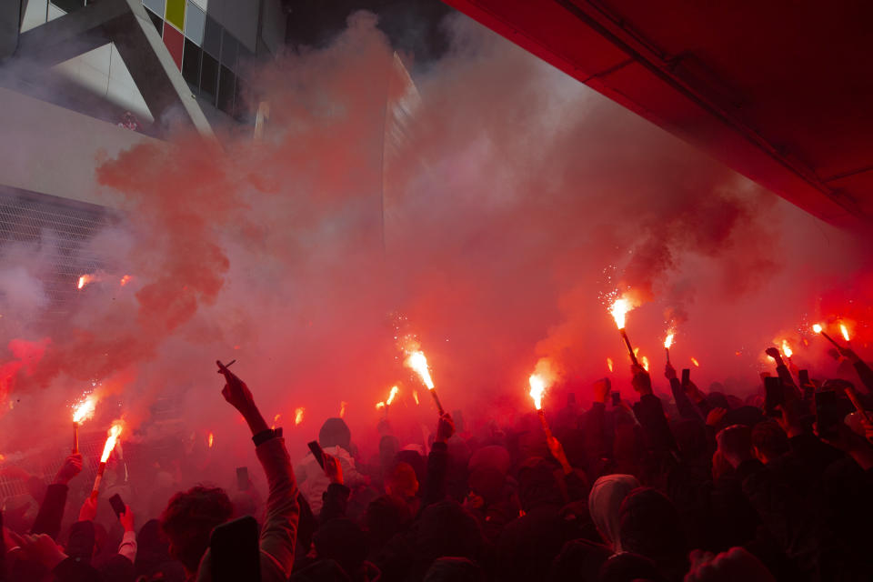 Ajax supporters set off flares as players show the trophy when clinching the Dutch Eredivisie Premier League title after winning the soccer match between Ajax and Emmen with a 4-0 score at the Johan Cruyff ArenA in Amsterdam, Netherlands, Sunday, May 2, 2021. (AP Photo/Peter Dejong)