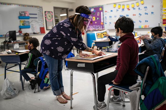 Teacher Elizabeth DeSantis, wearing a mask and face shield, helps a first grader during reading class at Stark Elementary School on September 16, 2020 in Stamford, Connecticut. (John Moore/Getty Images)