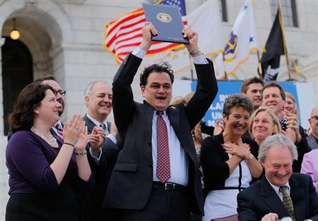 Speaker Gordon Fox holds up the Marriage Equality Act at the State House in Providence