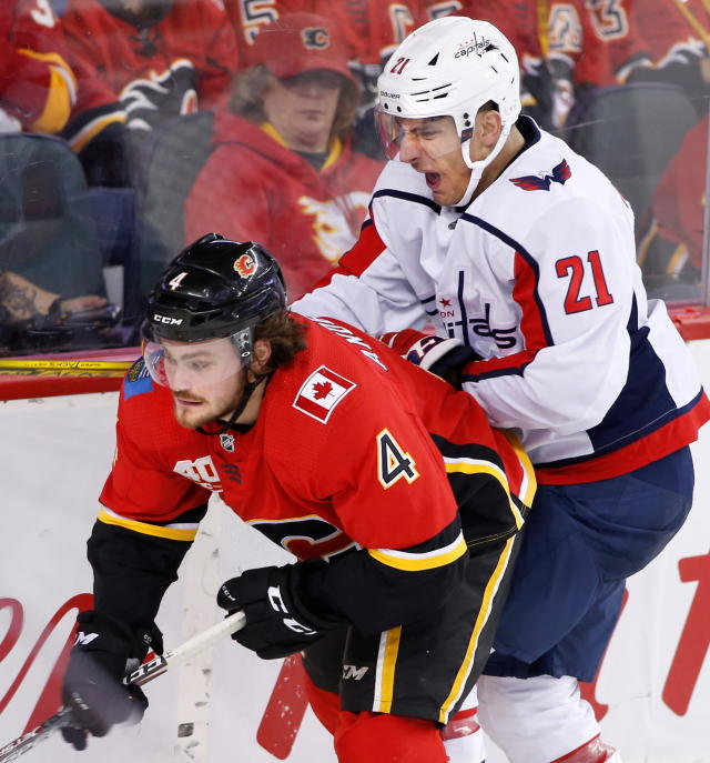 Calgary Flames defenseman Rasmus Andersson (4) and Washington Capitals right wing Garnet Hathaway (21) work along the boards during the second period of an NHL hockey game Tuesday, Oct. 22, 2019, in Calgary, Alberta. (Larry MacDougal/The Canadian Press via AP)