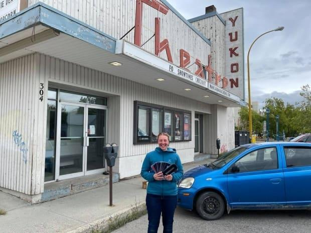 Pavlina Sudrich holds up the marquee letters she bought off eBay in front of the Yukon Cinema Centre in Whitehorse. She planned to update Qwanlin Cinema Centre's marquee  herself, before realizing she purchased the wrong size. (Dave White/CBC - image credit)