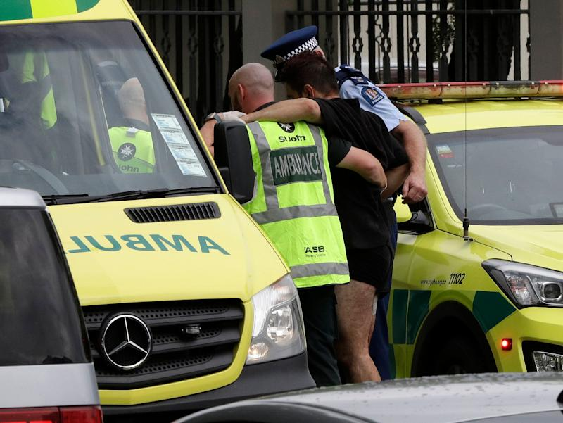 Police and ambulance staff help a wounded man from outside a mosque in central Christchurch, New Zealand, Friday, March 15, 2019. (Photo: Mark Baker/AP)