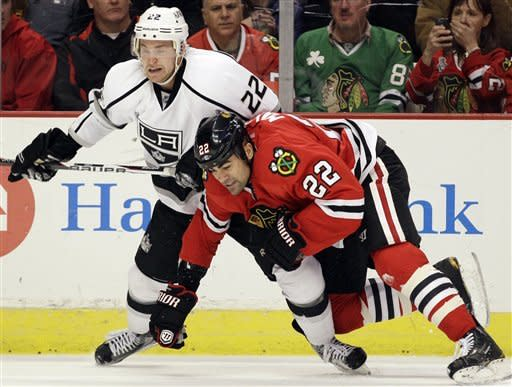 Los Angeles Kings' Trevor Lewis (22) and Chicago Blackhawks' Jamal Mayers (22) chase the puck during the second period of an NHL hockey game in Chicago on Wednesday, Dec. 28, 2011. (AP Photo/Nam Y. Huh)