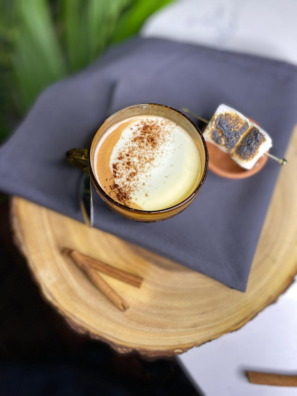 """<p>""""Cremosa de Cocoa is my favorite holiday drink at the moment,"""" says Chef Nelson German, owner of Afro-Latino cocktail Lounge <a href=""""https://www.sobremesaoak.com/"""" rel=""""nofollow noopener"""" target=""""_blank"""" data-ylk=""""slk:Sobre Mesa"""" class=""""link rapid-noclick-resp"""">Sobre Mesa</a>. """"I do want to shout out and mention my amazing Bar Manager Sadé Stamps for creating it. She wanted to create something festive but staying within our Afro-Latino concept.</p> <p>What I love about the cocktail is the childhood memories I get of times enjoying hot chocolate during the cold NYC winters. Especially when me and my cousins would sit around during Christmas before opening gifts sipping on hot chocolate. The coolest thing, though, is the addition of guava in the cocktail. I use to eat these amazing Dominican pastries that were a stuffed —""""Pan de Agua""""—with guava jam and chocolate. The cocktail brings me there.""""</p> <p>2 oz Corbin Cash Sweet Potato Liqueur</p> <p>1 oz Chairman's Reserve Spiced Rum</p> <p>1 oz red wine</p> <p>8 oz coconut milk</p> <p>7-8 oz semi-sweet Guittard chocolate</p> <p>2 oz marshmallow syrup</p> <p>4 oz marshmallows</p> <p>1 cinnamon stick</p> <p>1 pinch nutmeg</p> <p>1 tablespoon guava paste</p> <p>1 tablespoon sugar</p> <p>2 Allspice Berries</p> <p>chocolate powder</p> <p>Marshmallow syrup: In a saucepan whisk 4 oz marshmallows with 8 oz water over medium heat until well combined. Stir in cinnamon. Let cool before storing in the fridge. Keeps for 2 weeks. </p> <p>Rum sweet cream: In a bowl, using a hand mixer or whisk, whip cold whipping cream until it starts to thicken. Add 1 oz spiced rum and sugar, whip until just firm.</p> <p>Combine coconut milk, guava paste, chocolate, marshmallow syrup, wine, Allspice, and nutmeg in a saucepan over medium heat. Whisk until combined without allowing to boil. Remove from heat and stir in sweet potato liqueur. Strain and pour into a mug. Garnish with rum sweet cream and a sprinkle of chocolate powder. </p>"""