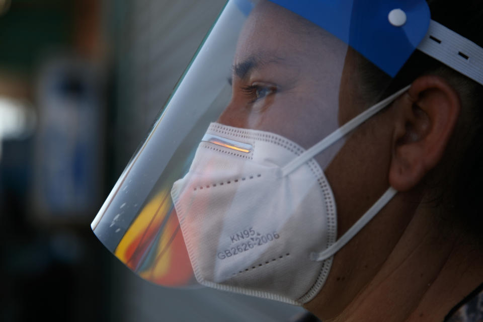Street vendor Laticia Ortega wears a plastic shield over her mask during the coronavirus pandemic in the Vermont Square neighborhood of Los Angeles, Thursday, May 21, 2020. While most of California took another step forward to partly reopen in time for Memorial Day weekend, Los Angeles County didn't join the party because the number of coronavirus cases has grown at a pace that leaves it unable to meet even the new, relaxed state standards for allowing additional businesses and recreational activities. (AP Photo/Jae C. Hong)
