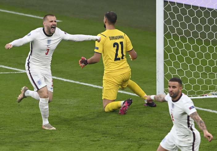 England's Luke Shaw, left, celebrates after scoring his side's opening goal during the Euro 2020 final soccer match between Italy and England at Wembley stadium in London, Sunday, July 11, 2021. (Facundo Arrizabalaga/Pool via AP)