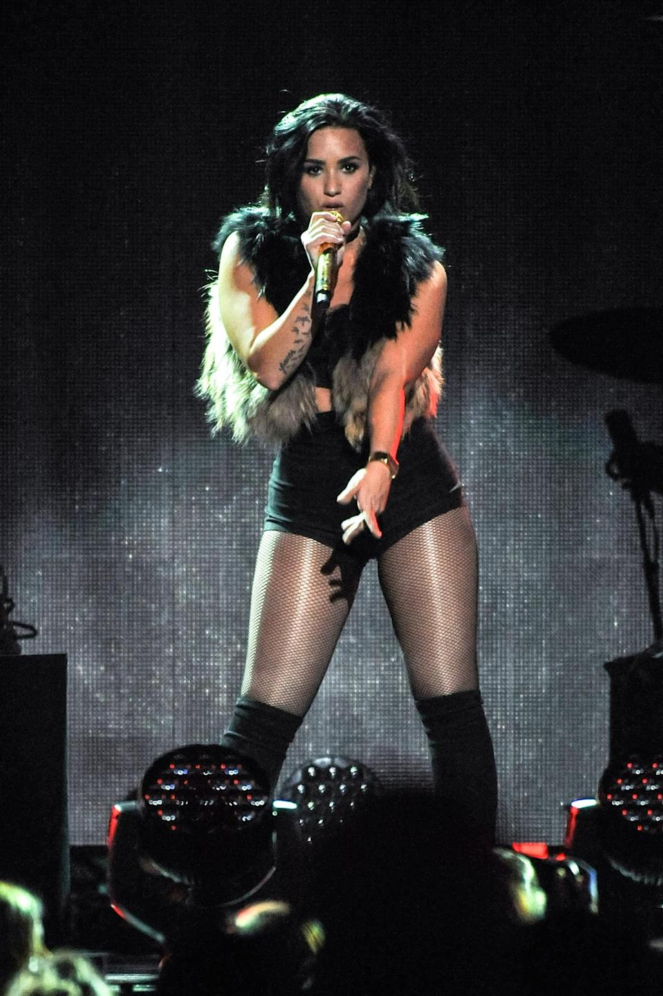 <p>Demi Lovato embodied confidence in this black crop top and hotpants combo, complete with over the knee boots and a furry vest.</p>