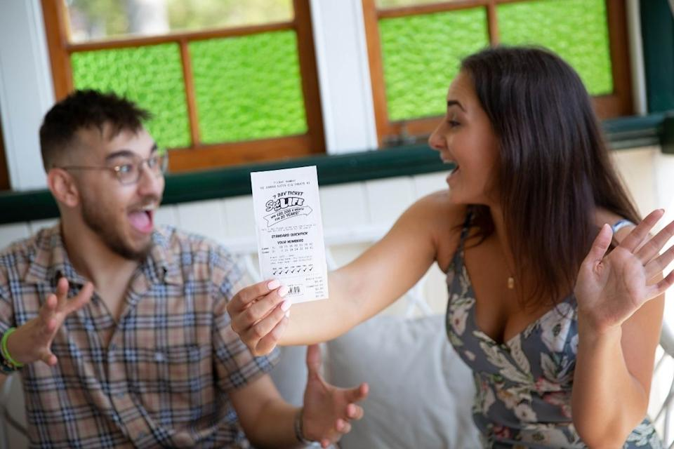 Couple holds up winning lottery ticket on the couch