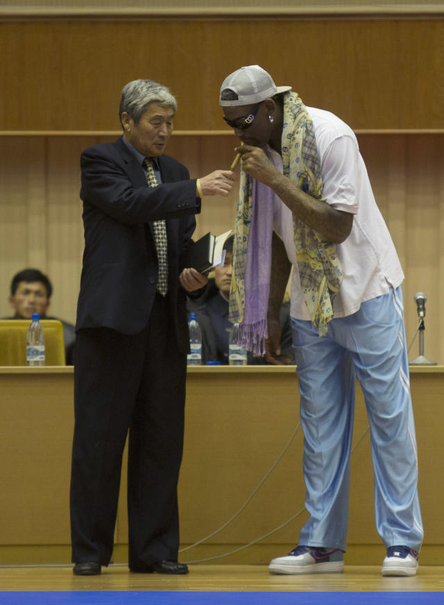 A North Korean official lights a cigar for Dennis Rodman at a basketball arena in Pyongyang, North Korea during a practice session for the US and North Korean team members on Tuesday, Jan. 7, 2014. Rodman came the North Korean capital with a squad of USA basketball stars for an exhibition game on Jan. 8, the birthday of North Korean leader Kim Jong Un. (AP Photo/Kim Kwang Hyon)