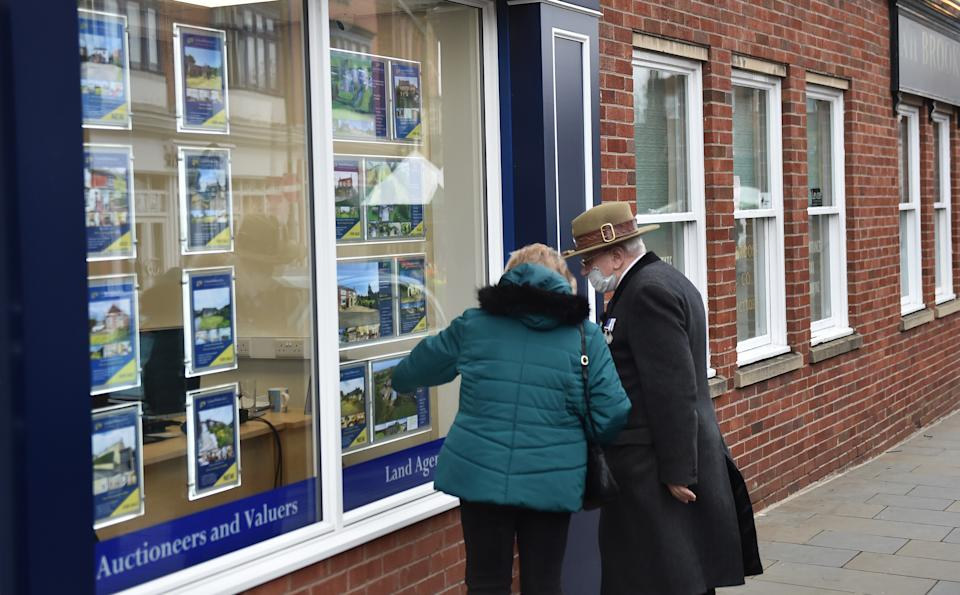 A couple look at houses for sale at an estate agents in Market Town of Leek, England. Photo: Nathan Stirk/Getty