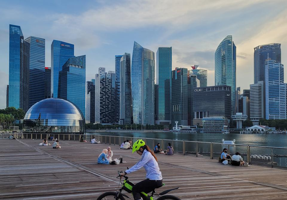 People relax on an outdoor deck as the sun sets in Marina Bay in Singapore on Monday, 14 June, 2021. Singapore begins to roll back a month of lockdown measures as average daily local COVID-19 cases come down from a May spike. Strict restrictions that disallow dining in at all food establishments and limit social interaction to groups not larger than 2 are expected to be rolled back in a week's time.  (Photo by Joseph Nair/NurPhoto via Getty Images)