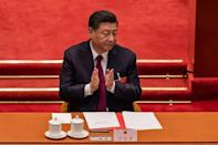 China's President Xi Jinping applauds after the National People's Congress changed Hong Kong's election system, something the US has vowed to raise