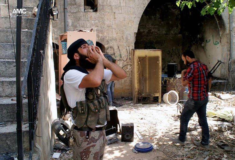 "This Tuesday, June 18, 2013 citizen journalism image provided by Aleppo Media Center AMC, which has been authenticated based on its contents and other AP reporting, shows a Syrian rebel shouting ""Allahu Akbar"" (God is Great) in the Old City of Aleppo, Syria. A group of U.S. Senators want to see the U.S. do more than provide arms to some of the outgunned rebels in the bloody civil war in Syria. Democratic Sens. Robert Menendez and Carl Levin and Republican John McCain say in a joint letter to Obama that the U.S. should consider targeting regime airfields, runways and aircraft, and help rebels establish safe zones in Syria. (AP Photo/Aleppo Media Center AMC)"