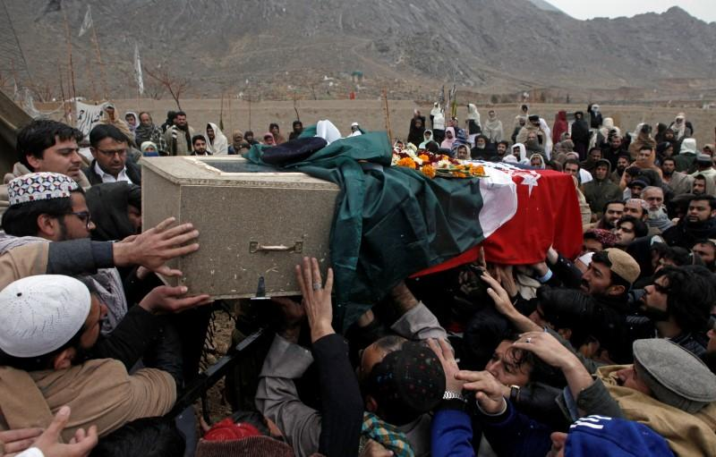 Relatives and neighbors reach out to carry the coffin of a police officer who was killed with others by a bomb blast in a mosque, during a funeral in Quetta