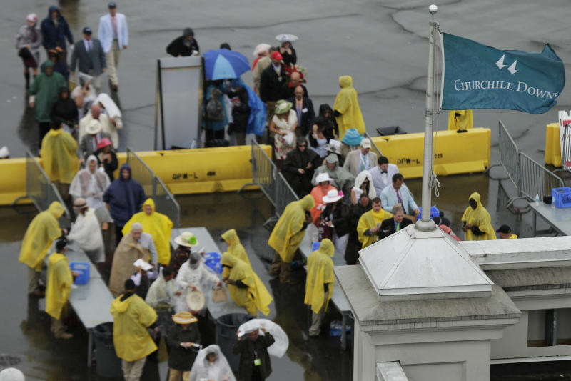 Spectators walk through security checks before entering Churchill Downs during the 139th Kentucky Derby Saturday, May 4, 2013, in Louisville, Ky. (AP Photo/Charlie Riedel)