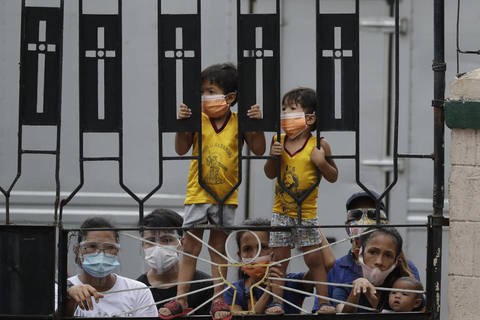 Young Catholic devotees wearing face masks to prevent the spread of the coronavirus stand try to get a glimpse of the the Black Nazarene at the Santa Cruz Church in Manila, Philippines a day before it's feast day on Friday Jan. 8, 2021. The annual Jan. 9 procession attended by tens of thousands of devotees has been cancelled amid the threat of the ongoing COVID-19 pandemic in one of Asia's biggest religious events. (AP Photo/Aaron Favila)