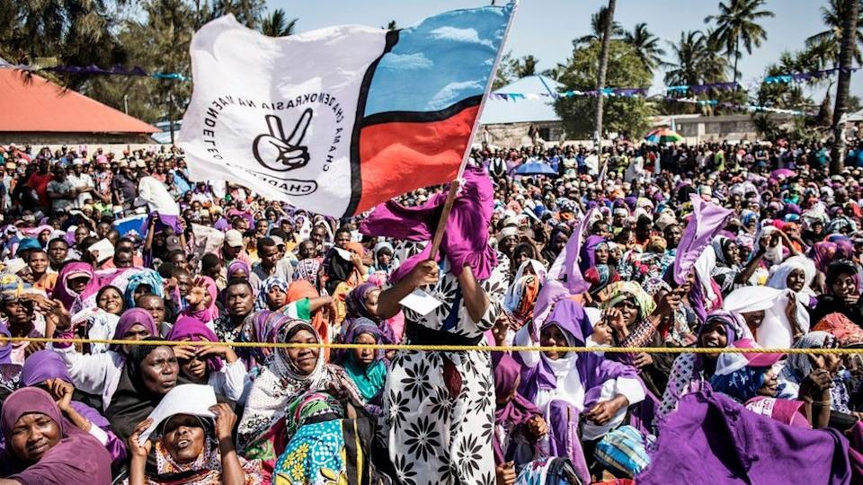 A women waves a flag of the Zanzibar opposition party, the Party for Democracy and Progress commonly known as Chadema, during a rally of opposition party Alliance for Change and Transparency (ACT) in Nungwi, on October 24, 2020.
