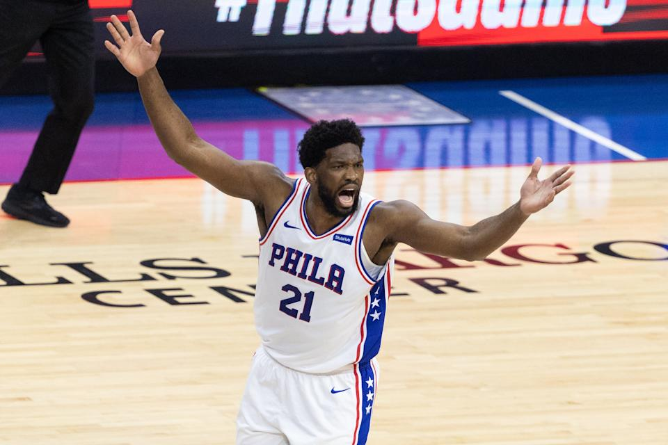 Joel Embiid with his arms in the arm reacting to a shot.