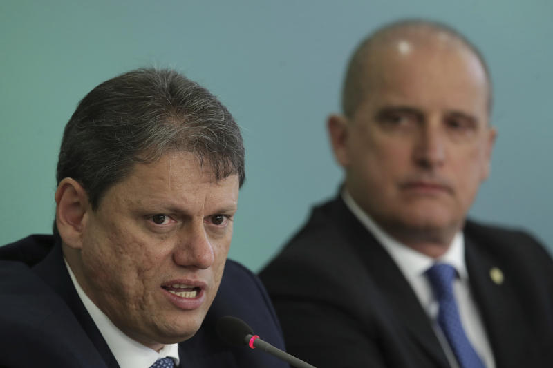 Brazil's Minister of Infrastructure Tarcisio Gomes de Freitas speaks at a press conference regarding a potential truckers' strike, at the Planalto Presidential Palace, in Brasilia, Brazil, Tuesday, April 16, 2019. The government of Brazilian President Jair Bolsonaro has announced a financial package aimed at staving off a potential truckers' strike. Pictured right is Chief of Staff Onyx Lorenzoni. (AP Photo/Eraldo Peres)