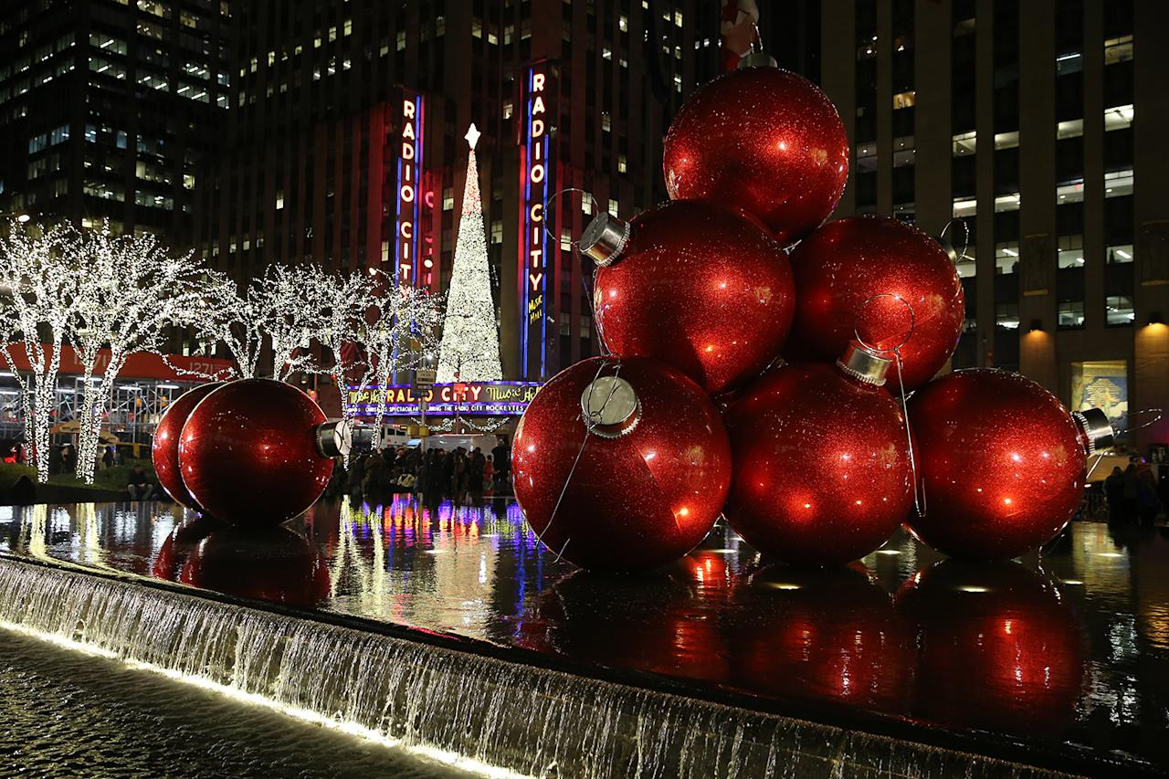 giant christmas ornaments rest in the fountain across the street from radio city