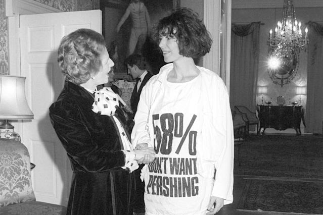 Prime Minister Margaret Thatcher greets fashion designer Katharine Hamnett, wearing a T-shirt with a nuclear missile protest message, at 10 Downing Street, where she hosted a reception for British Fashion Week designers. (Photo: PA Images via Getty Images)