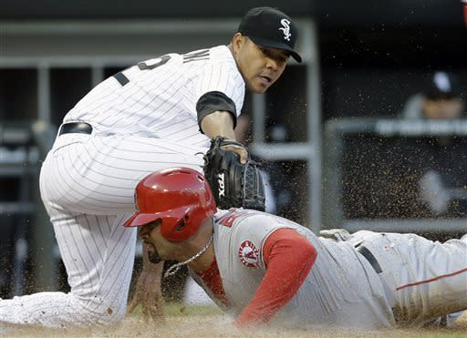 Los Angeles Angels' Albert Pujols, bottom, scores as Chicago White Sox pitcher Jose Quintana, top, applies a late tag during the third inning of a baseball game in Chicago, Saturday, May 11, 2013. (AP Photo/Nam Y. Huh)