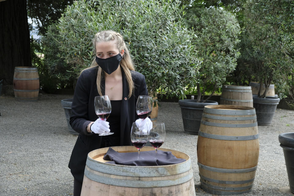 Wine educator Brooke Scheerer serves glasses of 2017 Edizione Pennino Zinfandel to guests at the Inglenook winery Friday, June 12, 2020, in Rutherford, Calif. California wineries started uncorking their bottles and welcoming people back to their tasting rooms Friday as the state's $145 billion tourism industry gears up with hotels, zoos, museums and aquariums also allowed to reopen. The historic winery, which dates to 1879, reopened Friday to wine club members after being closed since mid March because of the coronavirus threat and will be open to the public on June 25. (AP Photo/Eric Risberg)
