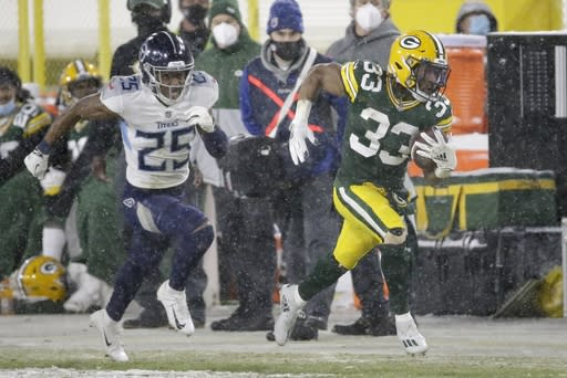Green Bay Packers' Aaron Jones tries to stay in bounds with Tennessee Titans' Adoree' Jackson pursuing during the second half of an NFL football game Sunday, Dec. 27, 2020, in Green Bay, Wis. (AP Photo/Mike Roemer)