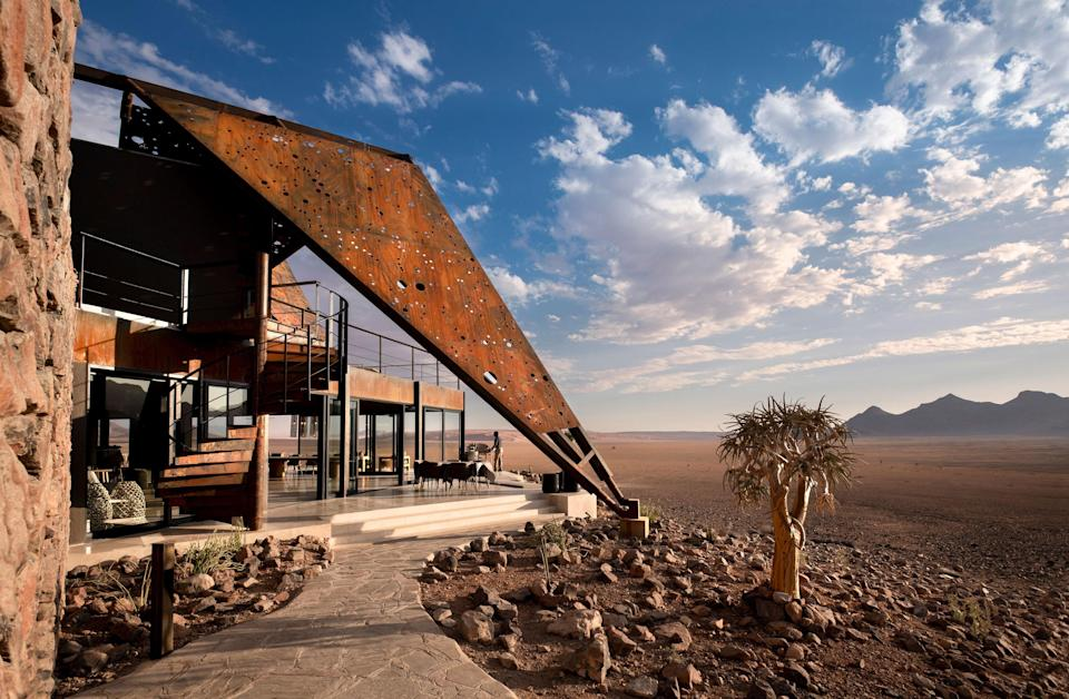 """<p><strong>Why did this hotel catch your attention? What's the vibe?</strong> The first impression of this lodge comes from the sky, as you drop down after about 1.5 hours in the air, over craggy canyons and khaki desert, barren save for the occasional leaf-less tree and ribbons of dried riverbed. Landing on the private airstrip (more sand, just with rocks organized to form an extra-long rectangle) the central building looks like a rusted sail, breaking out of the side of the lone hill and point in the direction of the equally burnt orange dunes directly opposite. From the strip, you can barely make out the 11 suites, peppered on either side of the lodge.</p> <p><strong>What's the backstory?</strong> Part of the andBeyond family, this lodge got a nine-month, $3 million rebuild—with only a few walls remaining from the original lodge and suites—to accommodate the dwindling animal population. While others lean into the excitement and energy of traditional safaris and game drives, andBeyond's lodge leans into the overwhelming quiet of southwestern Namibia, with a focus on relaxing (peppered by adrenaline-pumping ATV rides and dune hikes).</p> <p><strong>Tell us all about the accommodations. Any tips on what to book?</strong> The lodge has 10 one-bedroom suites and a singular two-bedroom suite. I was in one of the one-beds, which offer floor-to-ceiling, frameless windows that enclose nearly three sides of the suite (including the indoor shower) offering unfettered views of the passing wildlife and sparse flora. The interior decor is subdued, to match the exterior environs, with khakis, browns, and a few pops of black spread across the natural fabrics and furniture. There's plenty of room to spread out when the days get too hot, from chaise lounges alongside your own private plunge pool (kept at a nippy temperature to slow evaporation in the strong sun), to enveloping armchairs inside, pointed out towards the desert. My favorite feature was the <a href=""""https://www.cntrav"""