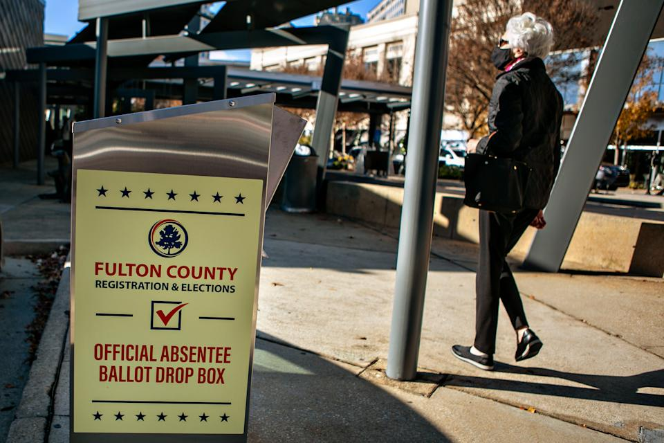 A voter arrives at the Buckhead library in Atlanta on the first day of In-person early voting for the Georgia Senate runoff election. (Jason Armond / Los Angeles Times via Getty Images)