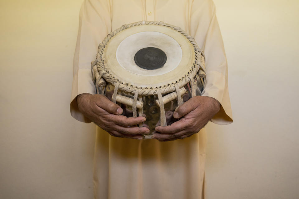 An Afghan musician holds a tabla during a portrait in Kabul, Afghanistan, Thursday, Sept. 16, 2021. About a month after the Taliban seized power in Afghanistan, the music is starting to go quiet. The last time that the militant group ruled the country, in the late 1990s, it outright banned music. (AP Photo/Bernat Armangue)