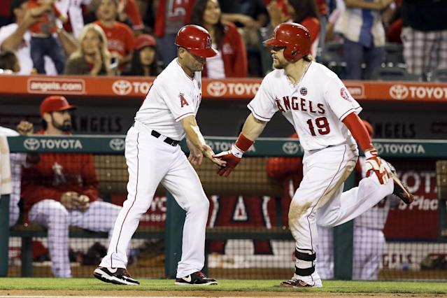 Los Angeles Angels' Collin Cowgill, right, is congratulated by coach Dino Ebel while rounding the bases on a solo home run against the Seattle Mariners in the fourth inning of a baseball game in Anaheim, Calif., Saturday, Sept. 21, 2013. (AP Photo/Reed Saxon)