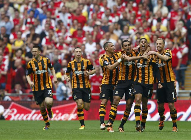 Hull City players celebrate with their team mate Curtis Davies (2R) after he scored his team's second goal against Arsenal during their FA Cup final soccer match at Wembley Stadium in London, May 17, 2014. REUTERS/Eddie Keogh (BRITAIN - Tags: SPORT SOCCER)