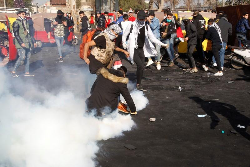 Iraqi demonstrators try to extinguish tear gas during the ongoing anti-government protests in Baghdad