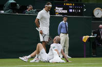 Switzerland's Roger Federer talks to Adrian Mannarino of France as he lies on the ground in pain during the men's singles first round match against on day two of the Wimbledon Tennis Championships in London, Tuesday June 29, 2021. (AP Photo/Kirsty Wigglesworth)