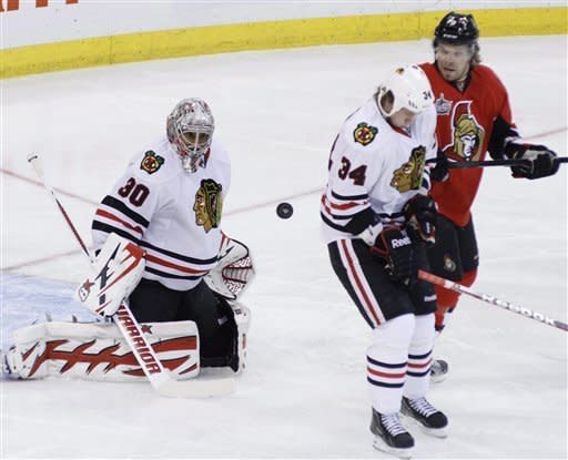 Chicago Blackhawks' Dylan Olsen, center, reacts to a flying puck as Blackhawks goaltender Ray Emery and Ottawa Senators' Milan Michalek, right, look on during first-period NHL hockey game action in Ottawa, Ontario, Friday, March 2, 2012. (AP Photo/The Canadian Press, Fred Chartrand)
