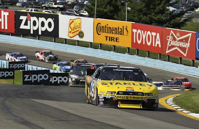Marcos Ambrose (09) leads the field through the esses on a restart during a NASCAR Nationwide Series auto race at Watkins Glen International, Saturday, Aug. 9, 2014, in Watkins Glen N.Y. Ambrose won the race. (AP Photo/Derik Hamilton)