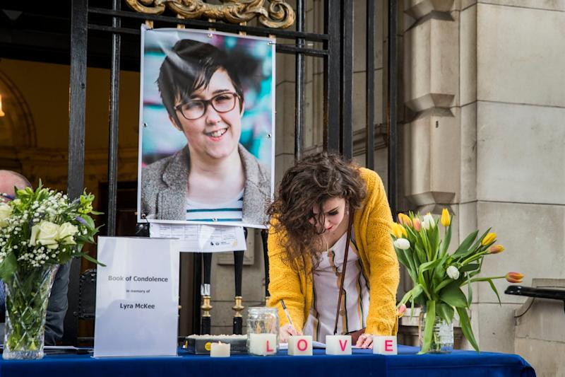 People signing a book of condolence after a vigil at Belfast City Hall in memory of murdered journalist Lyra McKee (PA)