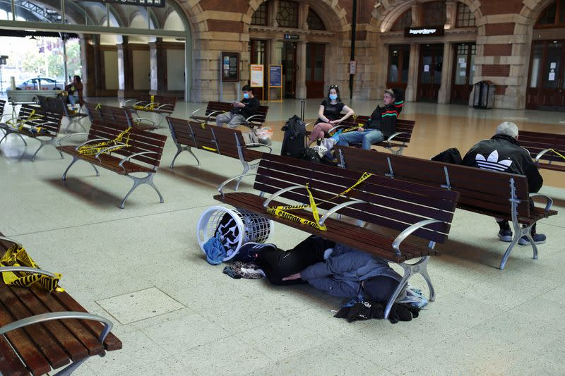 A homeless man sleeps under a bench at Sydney Central railway station during a workday following the implementation of stricter social-distancing and self-isolation rules to limit the spread of the coronavirus disease (COVID-19)