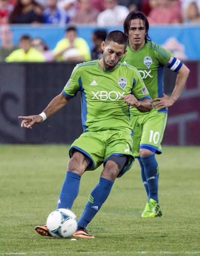 Seattle Sounders' Clint Dempsey, front, strikes a free kick against Toronto FC during first-half MLS soccer game action in Toronto, Saturday, Aug. 10, 2013. (AP Photo/The Canadian Press, Chris Young)
