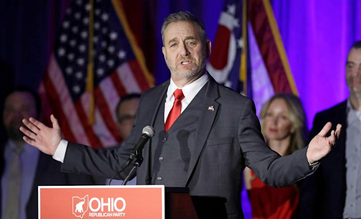 Ohio Attorney General Dave Yost in a suit raises his arms as he speaks to a crowd