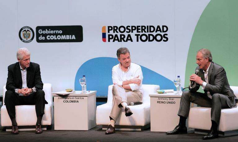 Former British Prime Minister Tony Blair (R) speaks next to Colombian President Juan Manuel Santos (C) and U.S. former president Bill Clinton (L) during the Third Way summit in Cartagena, on July 1, 2014, focused on the peace process in Colombia
