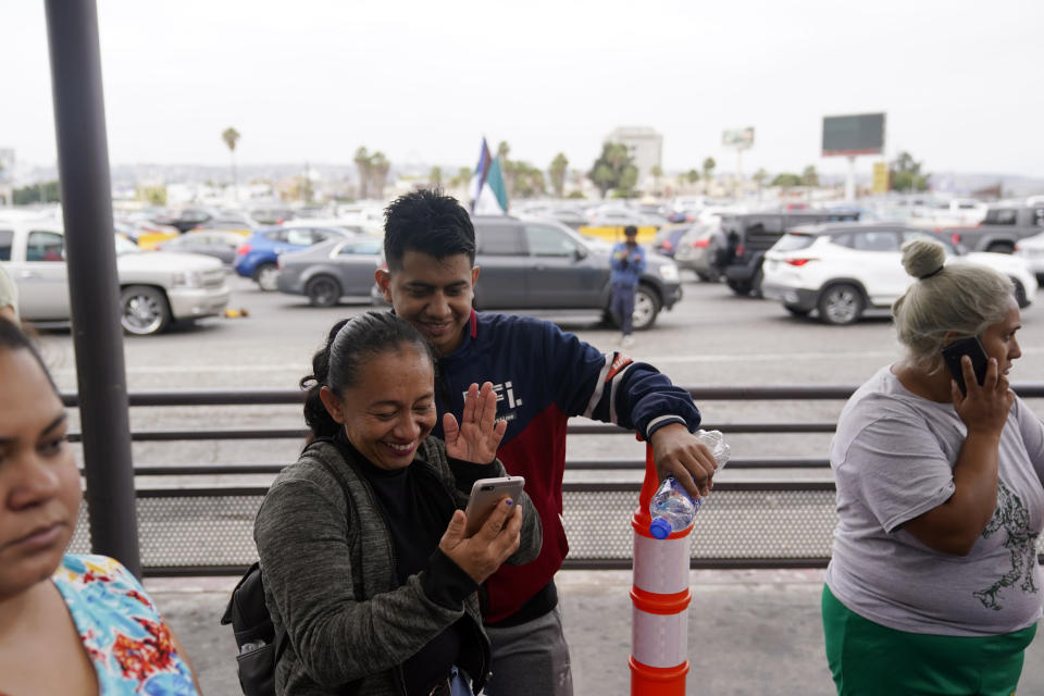 Lizeth Morales, second from left, waves alongside her husband, Nelson Membreno, second from right, during a video call with relatives in Honduras as they wait to cross into the United States to begin the asylum process Monday, July 5, 2021, in Tijuana, Mexico. Dozens of people are allowed into the U.S. twice a day at a San Diego border crossing, part of a system that the Biden administration cobbled together to start opening back up the asylum system in the U.S. Immigration advocates have been tasked with choosing which migrants can apply for a limited number of slots to claim humanitarian protection. (AP Photo/Gregory Bull)