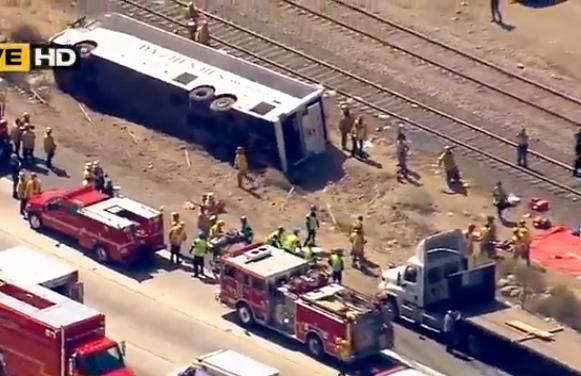 This video image provided by KABC-TV shows rescue officials working the scene of an accident where a tour bus, left, crashed and turned over injuring multiple passengers, Thursday Aug. 22, 2013 in Los Angeles. (AP Photo/KABC-TV)